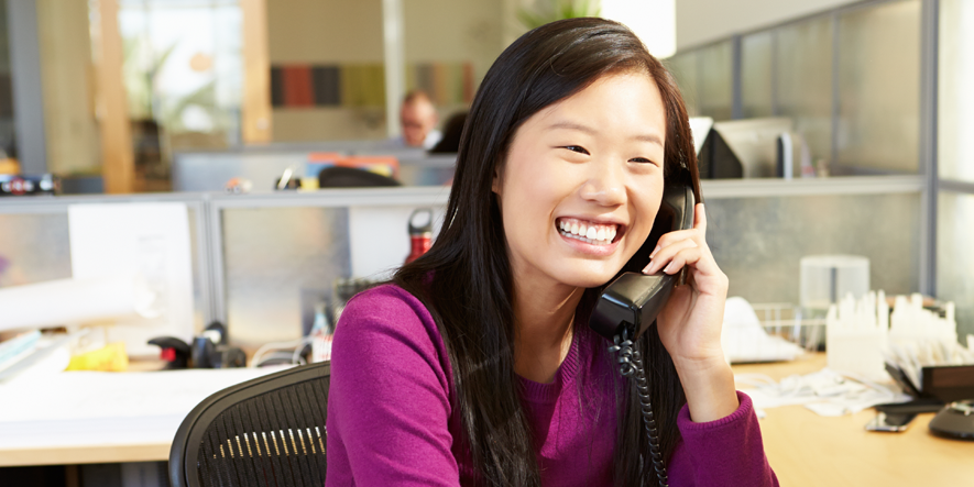 young office worker smiling brightly during a phone call with customer support rep- Open Access BPO